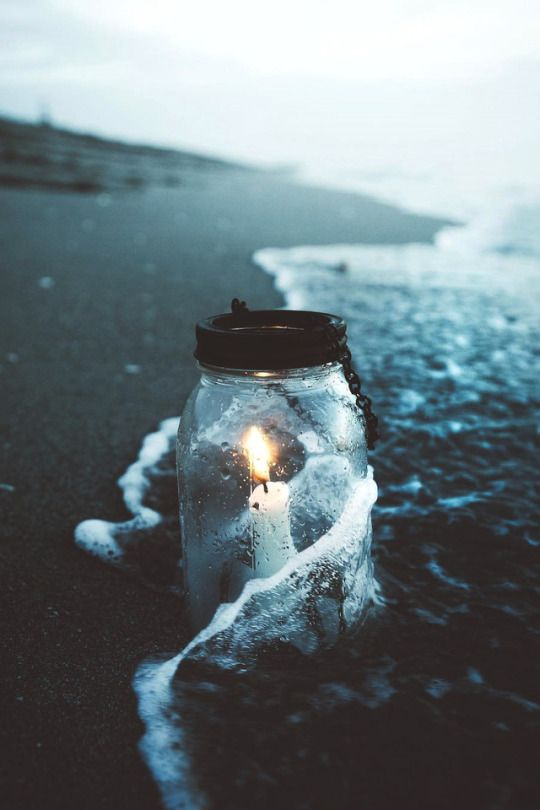 candle in a jar by the ocean